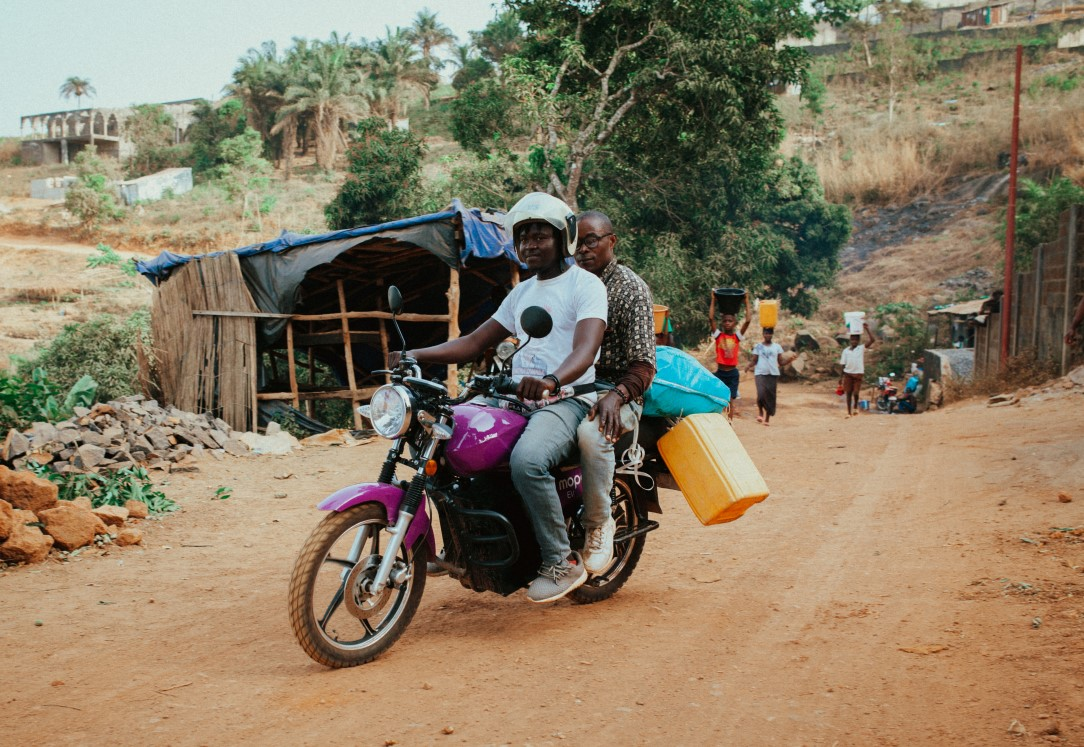 A MOPO e-motorbike being used for transportation of goods and people in rural Sierra Leone